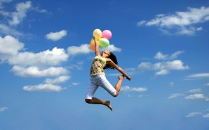 Happy young woman flying with colorful balloons